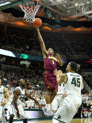 Minnesota Golden Gophers guard Andre Hollins (1) lays the ball up over Michigan State Spartans guard Denzel Valentine (45) during the 1st half of a game at Jack Breslin Student Events Center.