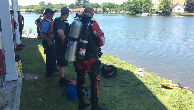 Dive teams prepare to enter the water to search for a woman who entered into a lake at an apartment complex in Wayne Township and never resurfaced, authorities said.