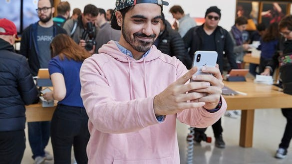 A man holding an iPhone X while looking at it.
