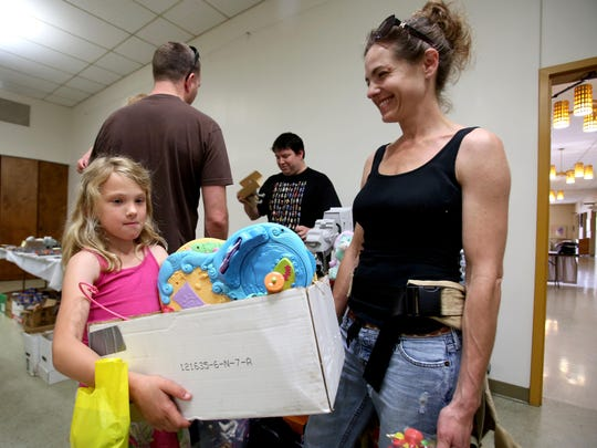 Taylor Billings, 7, carries the My Little Pony Butterfly Island playset she bought Sunday at the Willamette Valley Collector's Market as her mother, Rachel, looks on.