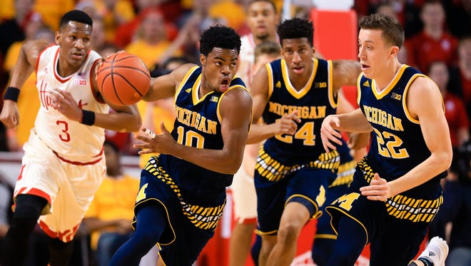Michigan's Derrick Walton Jr. (10) picks up a loose ball in front of Nebraska's Andrew White III (3) and teammates Duncan Robinson (22), and Aubrey Dawkins (24) during the first half of an NCAA college basketball game in Lincoln, Neb., Saturday, Jan. 23, 2016.