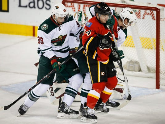 Minnesota Wild Nate Prosser, left, and Jonas Brodin, right, from Sweden, overpower Calgary Flames Jiri Hudler, from the Czech Republic, during second period NHL hockey action in Calgary, Thursday, Jan. 29, 2015. (AP Photo/The Canadian Press, Jeff McIntosh)