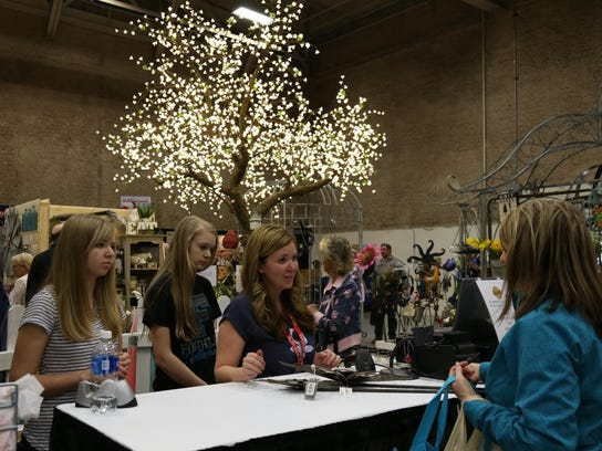From left, Makinsa, Braelyn and Monique Eakman help a customer at the Real Deals booth at the annual Home and Garden Show.