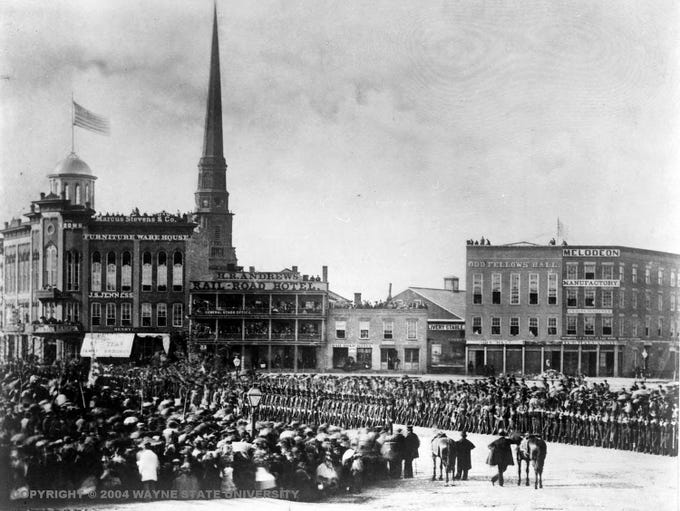 Woodward Avenue and its surroundings have gone through many transformations over the years. Here, people attend the presentation of colors to the 1st Michigan Infantry at their departure May 11, 1861, at Campus Martius. Buildings such as Andrews Rail Road Hotel and Marcus Stevens & Co. can be seen in the background.