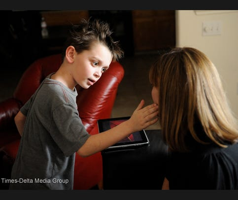Max Cutler, 7, who has autism, touches his mother's face as a nonverbal way to ask her to say a word aloud for something that he sees on his iPad. Sometimes the words are in French and Spanish as well as English, Sherry Cutler, his mother, explained.