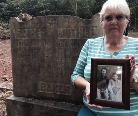 Earlene Cullen and other relatives hope to keep the grave sites of 10 ancestors undisturbed in a family cemetery in Avery's Creek. She's holding a picture of her great-grandparents buried beneath this headstone, John Milton and Melinda Baker. The land fell out of family ownership decades ago, and a new owner wants to develop the land for housing. The new owner says he'll pay to move the deceased to another cemetery, but descendants want the caskets and vaults to remain where they are.