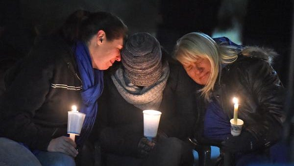 Ashley Deane, center, the mother of the two children killed in a home shooting in Reno, is comforted as the Reno community gathered for a candlelight vigil on Sunday night Nov. 16, 2014 to remember the two children.