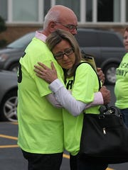 "Angela and Steve Wesener hug outside the Edgar school building before they, supporters and friends attended the Edgar School Board meeting where a new bullying policy was under discussion in June 2015. Their t-shirts read ""We are Jonny."""