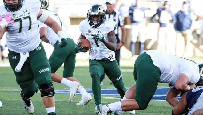 CSU running back Dalyn Dawkins follows the block of center Jake Bennett (77) through the hole during the Rams' 27-14 win Saturday at Utah State.