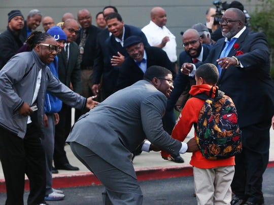 """About 70 men from the community lined the walkway leading to Tindley Preparatory Academy at the start of the school day on Oct. 5, 2015, to form a """"high-five line"""" to greet and encourage arriving students and demonstrate that the Indianapolis community cares about them."""