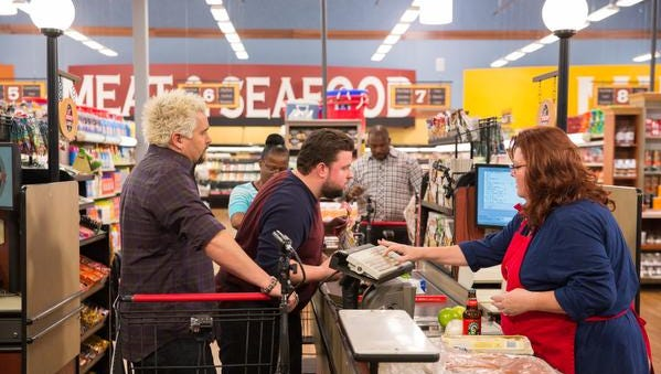Host Guy Fieri at the check out line with Chefs Robbie Jester, Beatrice Guillory, and Erick Williams during Game 1, Budget Battle, as seen on Food Network's Guy's Grocery Games, Season 6.