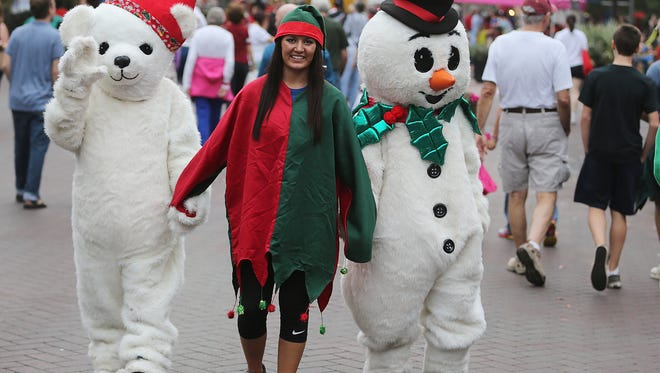 A Winter Festival attendee holds hands with a Christmas bear and snowman at the 2013 Winter Festival. The 2015 Winter Festival takes place on Saturday.