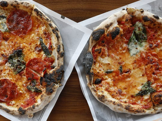The Enquirer/Cara Owsley The Diavola, left, a red pizza with smoked mozzarella, pepperoni, basil and chili flake; and the Margherita at Pizzeria Locale. The Diavola, a red pizza with smoked mozzarella, pepperoni, basil and chili flake by Pizzeria Locale at 7800 Montgomery Road in Kenwood.