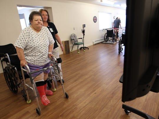 Patty Selaya, 69, kicks the soccer ball on the screen