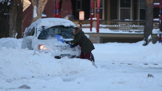 Abby Stavish of Harvard Street tries to dig out her sport utility vehicle to get to work.