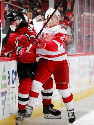 Joe Hicketts of the Detroit Red Wings hits Marcus Johansson of the New Jersey Devils in the third period in his NHL debut Monday.