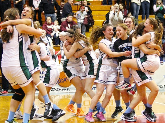 Members of the Mount St. Joseph girls basketball team celebrate its 35-29 win over Proctor in the Division IV high school state championship game at Barre Auditorium last year.