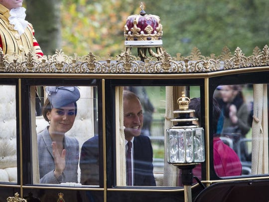Duchess Kate waves from a Scottish State Carriage in procession down the Mall to Buckingham Palace state visit of Singapore's President in London on Oct. 21.