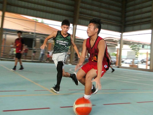 636673770345885021-U16-Team-Unity-s-Sean-Cuenco-brings-the-ball-down-the-court-as-Sinajana-Rockers-Chuckie-White-defends.JPG