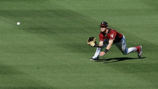 Arizona Diamondbacks center fielder Evan Marzilli catches a fly ball hit by Los Angeles Dodgers' Yasiel Puig during the fifth inning of a spring training baseball game in Scottsdale, Ariz., Friday, March 18, 2016.