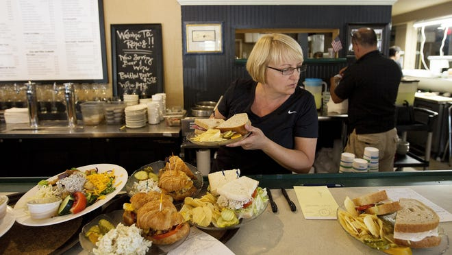 Jackie Stazio sorts through lunch orders at Rene's, where the menu stayed the same despite a move.