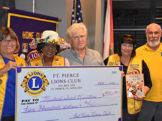 Lions Club memberspresent Mustard Seed with a check
