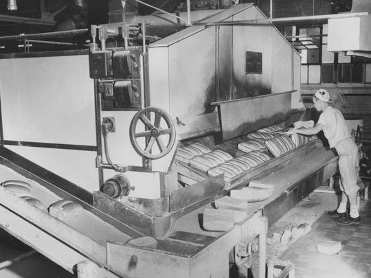 Omar Bakery employee pulling freshly baked loaves of bread from the 500-degree oven in 1953.
