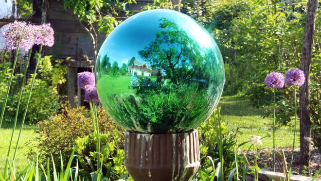 Agreen-tinted gazing globe visually takes in all of last summer's garden in New Paltz, New York. These mirrored glass ornaments fell out of favor about 50 years ago, but are making a comeback, seen by some as attractive ornaments and by others as kitsch.