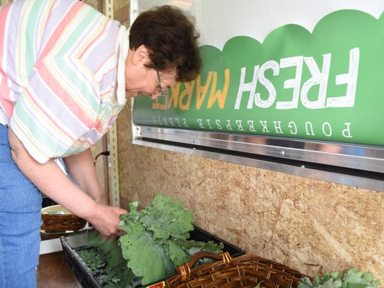 Volunteer Betty Olson, 72, of Clinton, bundles up collard greens inside the mobile farmers market on Thursday.  Poughkeepsie Plenty Fresh Market launches their mobile farmers market on Thursday at the Family Partnership Center in Poughkeepsie.