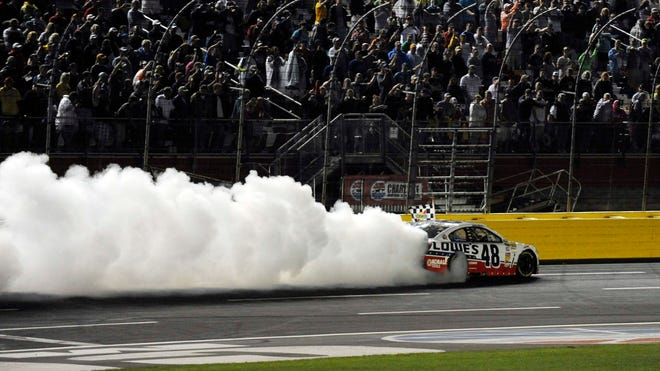 Jimmie Johnson does a burnout after winning NASCAR's exhibition for all-stars in 2013.