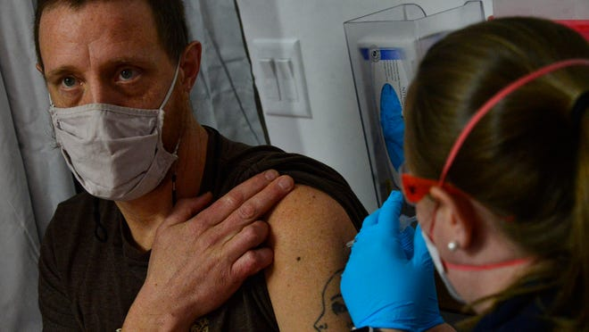 Matt Chapman, a classroom assistant at Marlboro Elementary in Marlboro, Vt., looks away as Emily Stone, an emergency medical technician with Rescue Inc., gives him the first dose of the Pfizer COVID-19 vaccine during a vaccination clinic at Leland & Gray Union Middle and High School on Friday.