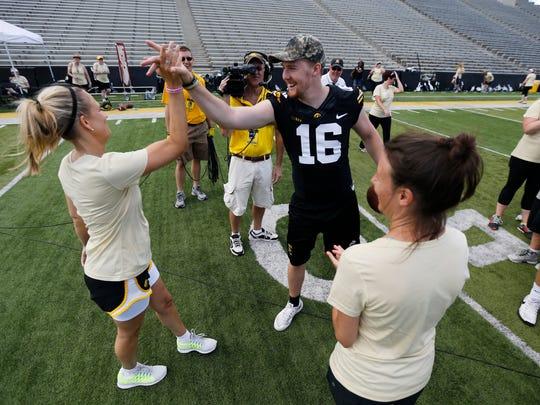 Iowa quarterback C.J. Beathard high-fives his mother, Susan, at the Iowa Ladies Football Academy on Saturday.