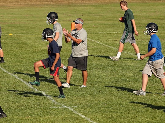 Klahowya head coach Dan Ericson (center) pumps up his