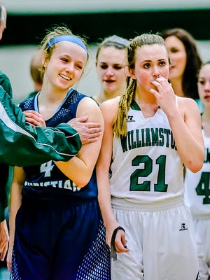 Jennifer DeBoer ,left, of Grand Rapids South Christian smiles as an unhappy Halle Wisbiski ,21, of Williamston walks off the court after the Grand Rapids South Christian 6 point win in their Class B regional semifinal game Tuesday March 8, 2016 at Wayland Union High in Wayland.