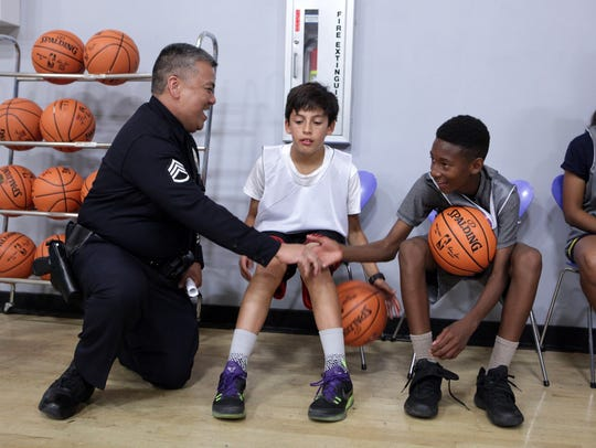 A police officer and youth participants talk during