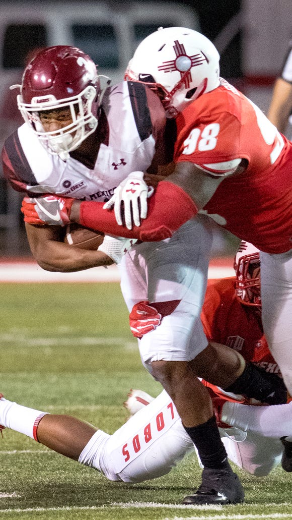 Aggies running back Larry Rose III drags a couple of UNM defensive players for a few extra yards during the fourth quarter of play Saturday night at Dreamstyle Stadium in Albuquerque. 9/9/17Gary Mook/ for the Sun-News