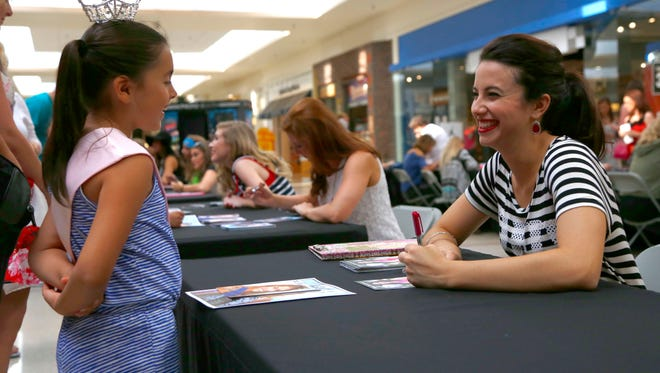 Iris McConnell, 7, talks with Ms. Northwestern Ohio, Hayley Hesselschwardt  during an autograph session at Richland Mall on Saturday afternoon.
