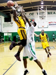 Natchitoches Central's Brian White tries to get the ball past Bossier City's Abarreion Johnson during their game Tuesday evening.