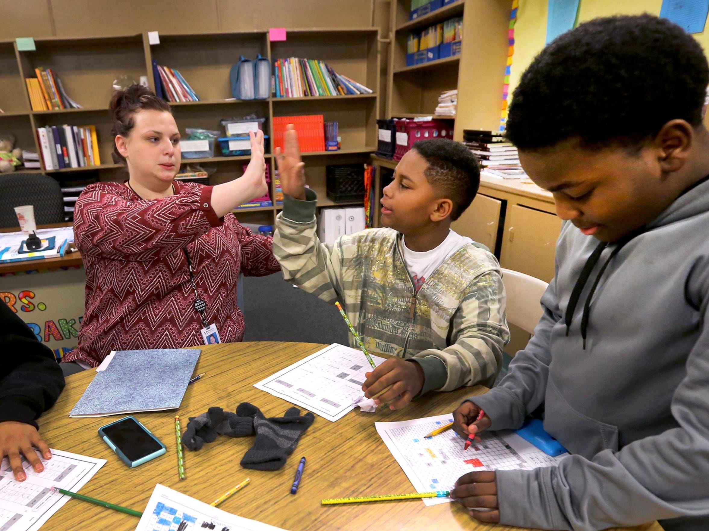 Cortney Cagle, left, a tutoring coordinator at Bradley Academy, gives Daquan Malone, center, a high-five after answering a question right as Malone works on a worksheet during the Bradley Academy After School Tutoring Program, on Friday, Jan. 8, 2016. Keino Franklin, right, works on his math worksheet during the program.