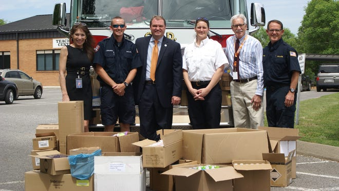 Mayor Paige Brown, Sumner County Director of Schools Del Phillips, Family Resource Center for Sumner County Schools Director Mike Shelton and members of the Gallatin Fire Department with some of the items collected during the departments toiletry drive benefit underprivileged students.