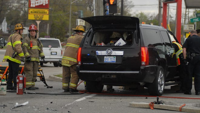 Port Huron firefighters and police work on a vehicle involved in an accident at Hancock Street and Pine Grove Avenue