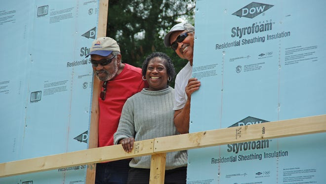 Priscilla McDow, center, is a Habitat future homeowner, once she completes the required 200 hours of homeowner education and hands-on volunteer time on her home.
