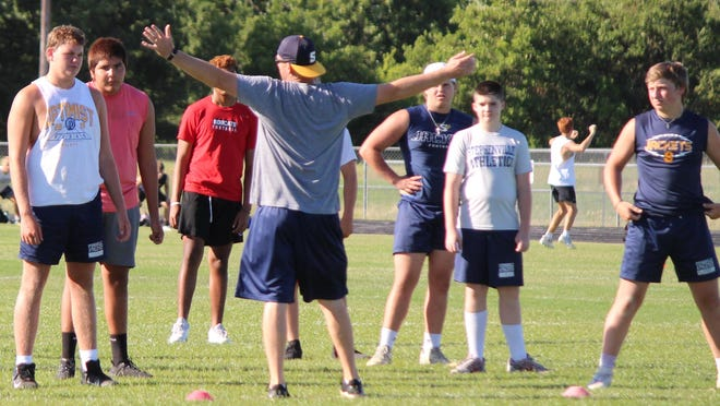 Stephenville High School football players receive instructions from a coach during offseason conditioning workouts at Henderson Junior High School. On Monday, the Yellow Jackets and Honeybees will begin their official preseason workouts for football, volleyball, cross country and team tennis.