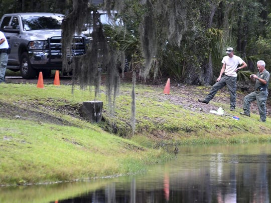 Law enforcement with South Carolina Department of Natural Resources take pictures of the site where authorities say Cassandra Cline was dragged into a lagoon by an alligator and killed while trying to save her dog Monday on Hilton Head Island, S.C.