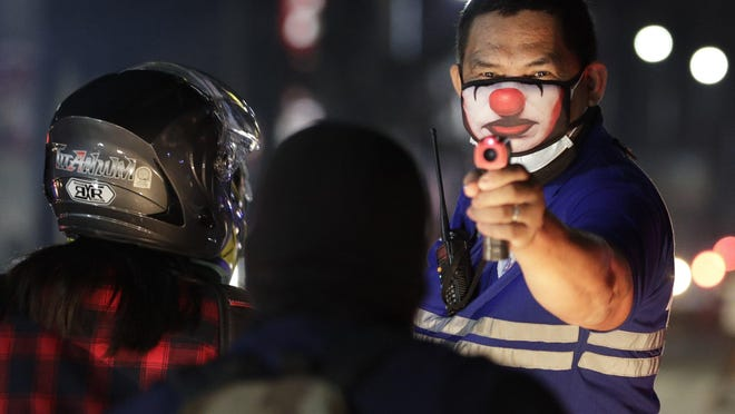 FILE - In this March 16, 2020, file photo, a village official wearing a protective mask uses a thermal scanner at a checkpoint as part of a precautionary measure against the spread of the new coronavirus in the outskirts of Manila, Philippines. As governments across the world enact emergency measures to keep people at home and stave off the pandemic, some are unhappy about having their missteps publicized. Others are taking advantage of the crisis to silence critics and tighten control. At least two Filipino reporters have been charged by police with spreading false information about the crisis.