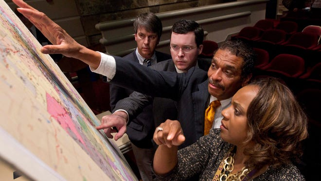 Alabama lawmakers study a map of the proposed redistricting plan crafted by the Republican state Legislature in 2012.