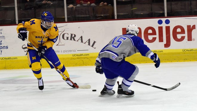 Aiden Krueger of Moeller sends the puck past St. Xavier's Roope Ketola (15) on a pass play.