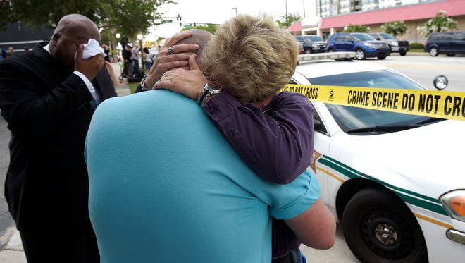 Terry DeCarlo, executive director of the LGBT Center of Central Florida, center, is comforted by Orlando City Commissioner Patty Sheehan, right, after a shooting involving multiple fatalities at a nightclub in Orlando, Fla., Sunday, June 12, 2016.