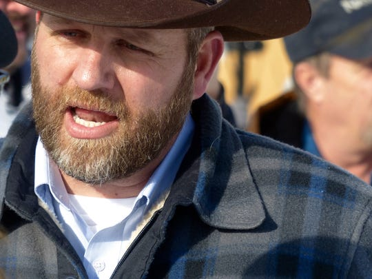 Ammon Bundy chats with a protester Saturday, Jan. 2, 2016, during a march on behalf of a Harney County ranching family in Burns, Ore. Bundy, the son of Nevada rancher Cliven Bundy, who was involved in a standoff with the government over grazing rights, told The Oregonian that he and two of his brothers were among a group of dozens of people occupying the headquarters of the Malheur National Wildlife Refuge.