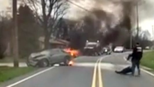 In this screen grab taken from a dashcam video, veteran firefighter Nate Tracey is seen pulling a man out of and away from a burning car in York Township on Monday. Tracey is the volunteer fire chief at Goodwill Fire Company.